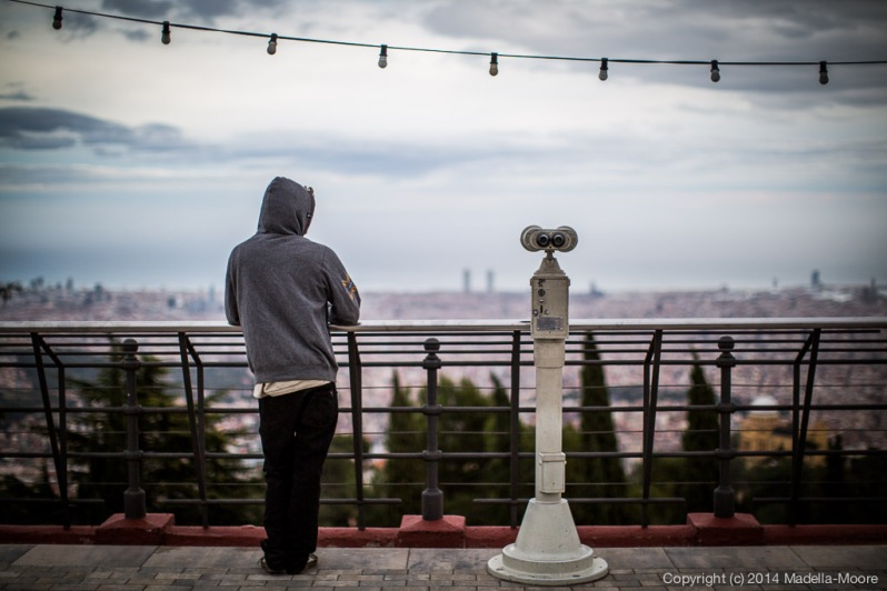 Person and binocular stand, gazing wistfully over Barcelona towards the sea.