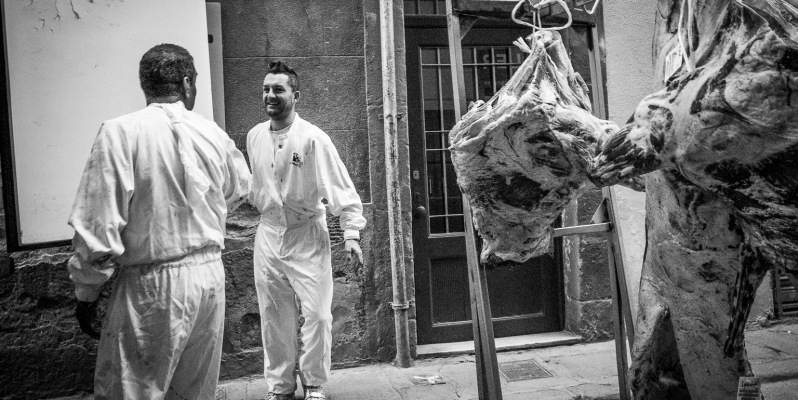 Two market workers delivering animal carcasses