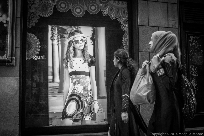 Ideals - Muslim women looking at a fashion model . Barcelona Street Photography