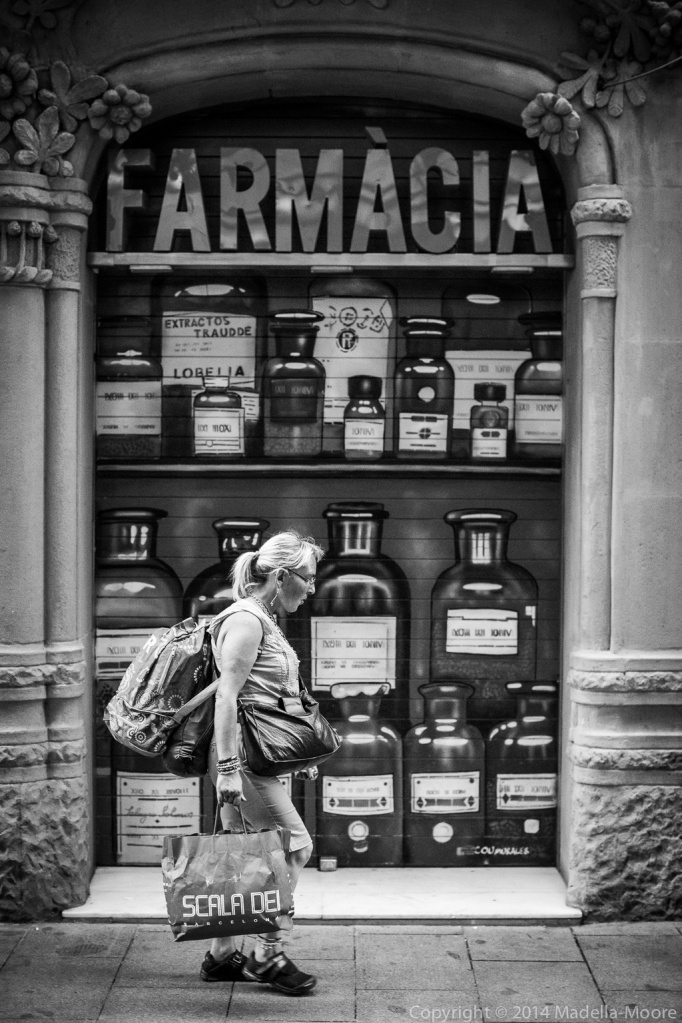Heavily laden woman in front of pharmacy with painted bottles