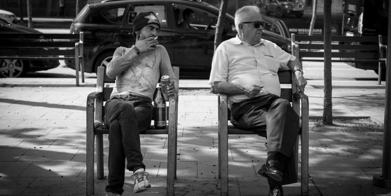 Two men sitting awkwardly on a Bench, Plaça de la Universitat, Barcelona.