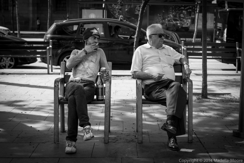 Two men sitting awkwardly on a Bench, Plaça de la Universitat, Barcelona.