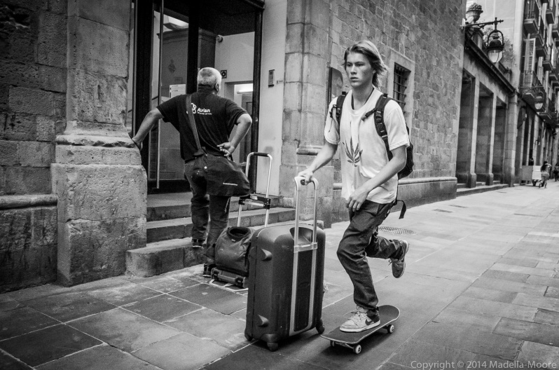 Skateboarder with roller luggage, Barcelona