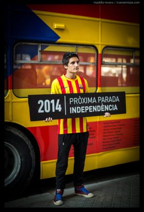 "Person standing in front of a bus painted as a Catalan flag and holding a sign ""next stop: independence""."