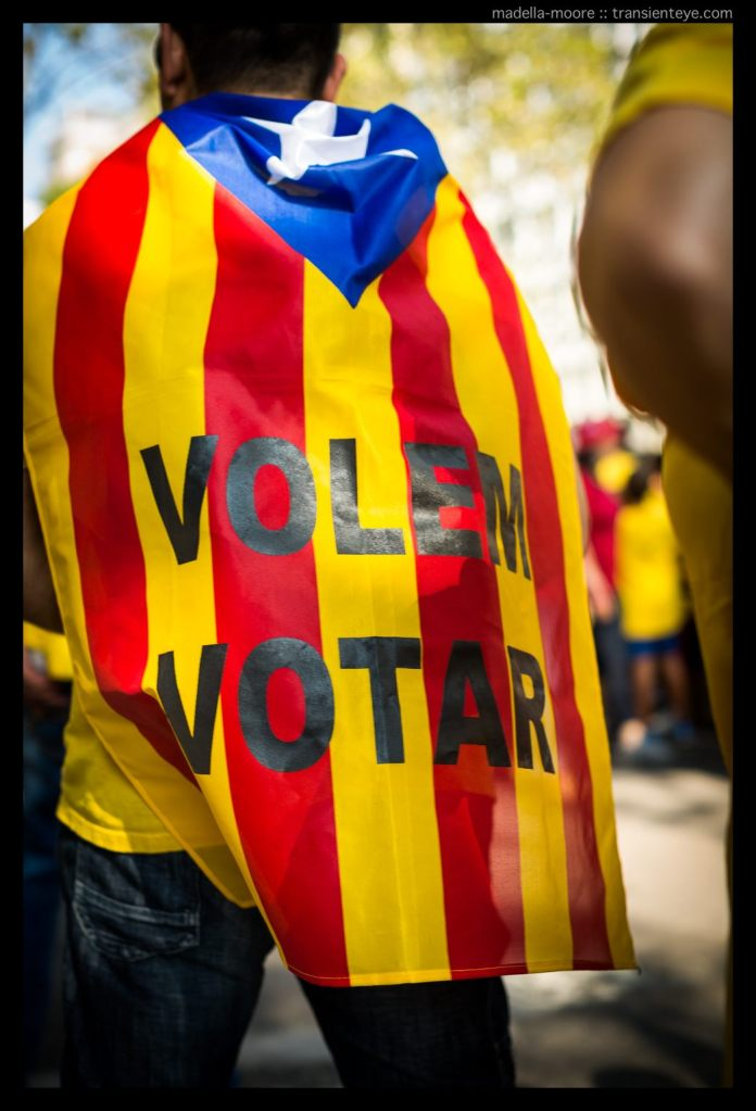 Person wearing a Catalan flag with the text Volem Votar (we want to vote)