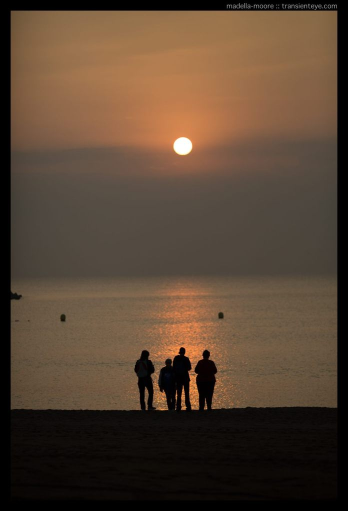 Silhouettes of people watching the sun rise over the Mediterranean at Port Olympic, Barcelona
