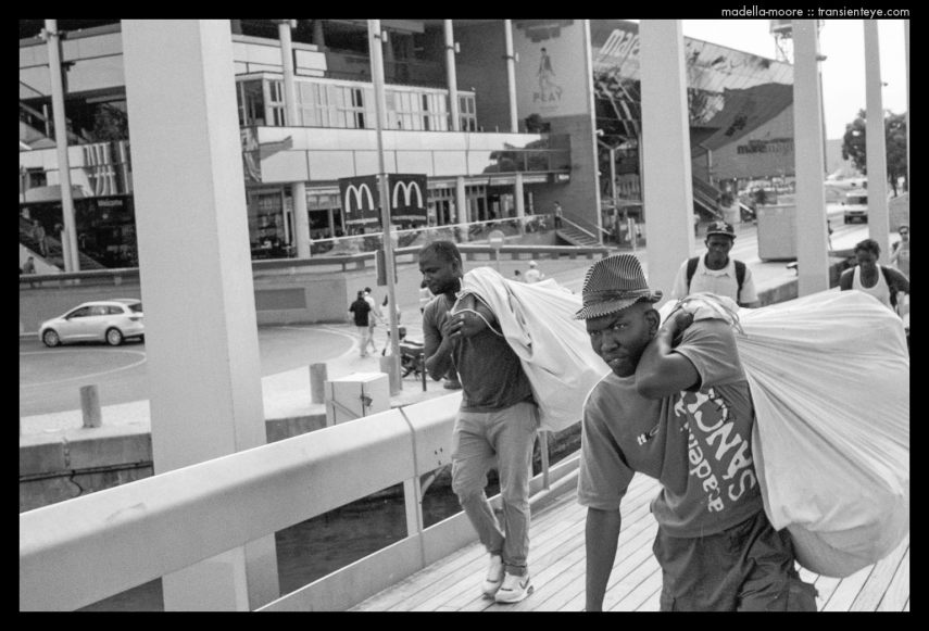 Escaping street sellers, Port Vell. Ilford HP5+. Leica M7. Zeiss ZM 1.5/50.