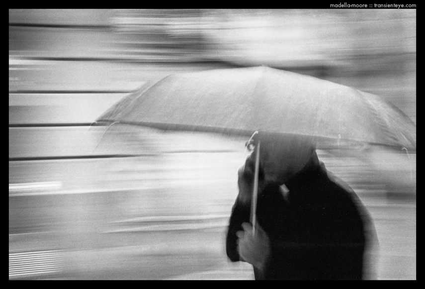 Motion-Blurred Image of a  Priest in the Rain under an umbrella