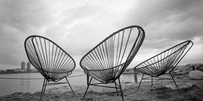 Three string chairs, on the beachfront at Barceloneta.