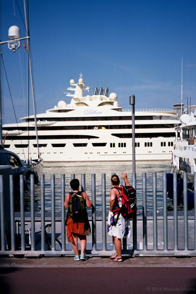 People looking at a luxury yacht behind a security fence, Barceloneta