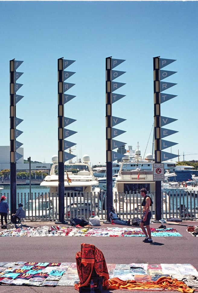 Illegal street-sellers in front of a luxury yacht, Barceloneta.