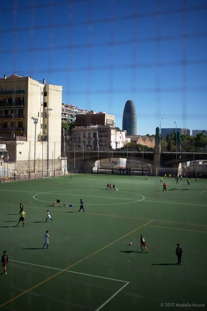 Torre Glòries, seen from a football ground in Fort Pienc, Barcelona.